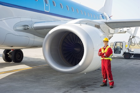 Jet engine mechanic posing next to a commercial aircraft on the runway photo