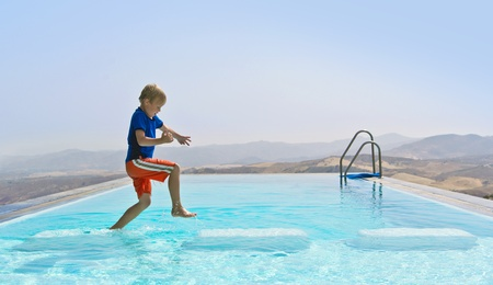 Boy Playing In a Swimming Pool, hopping from stepping stone to stepping stone Outdoors