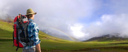 awe: Hiker being overwhelmed and in awe of the Icelandic landscape that surrounds him. A rainbow appearing in a shower from the low clouds over the lush green meadows