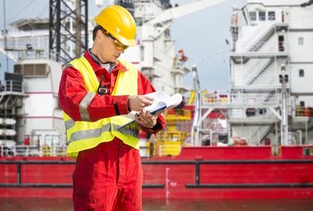 Sicherheit Offizier, stand vor einem riesigen industriellen Plattform, tragen Overalls, ein Helm, eine Schutzbrille und ein Klemmbrett mit Checklisten