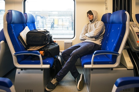 backpackers: Young Man Sleeping In Train With Luggage  Stock Photo
