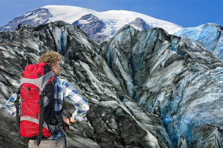 Hiker overlooking the huge crevases and rugged terrain of the the glacier he's about to climb, absorbing the sheer challenge he's facing photo