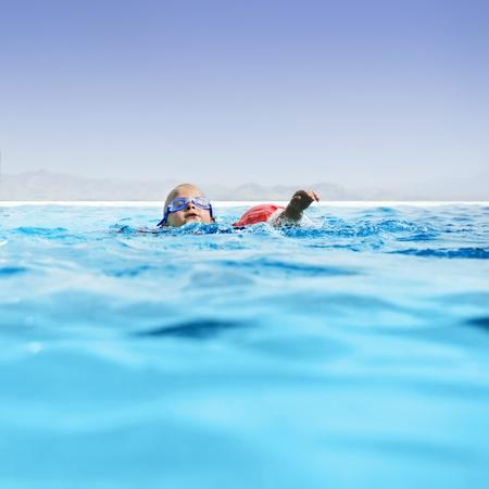 Giovane ragazzo che imparare a nuotare in una piscina infinty lusso.