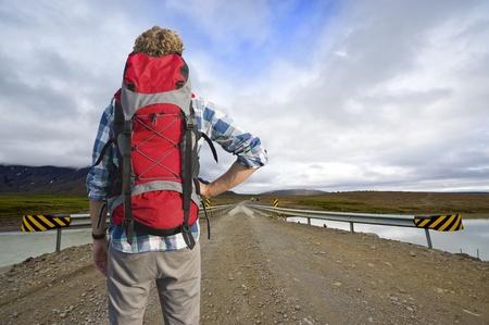 Müde Wanderer, mit einer Niederlage Pose, sieht über eine Brücke an der Bus nach Hause, so dass aus der Mitte von Nirgendwo.
