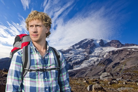 rugged terrain: Mountaineer with a backpack keeping an eye out for weather changes Stock Photo