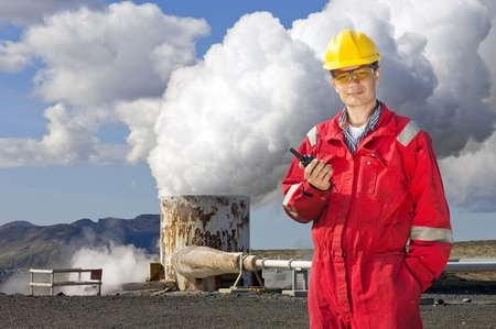 cb: Engineer with cb radio standing next to the violently emitting tube of a geothermical energy plant