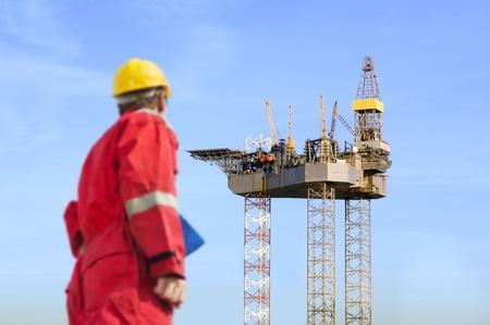 torres petroleras: Roughneck (fuera de foco) mirando una enorme plataforma petrolera se está construyendo. Foto de archivo
