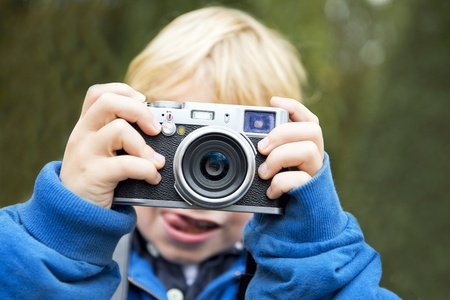 rangefinder: Young photographer, holding a retro rangefinder camera in front of his face, taking a picture Stock Photo