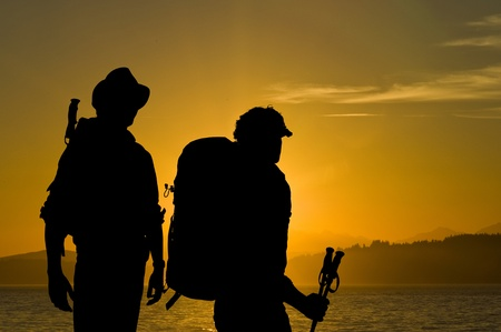 adventurers: Silhouette of two adventurers admiring the radiant sunset over a lake with hills and forests in the background