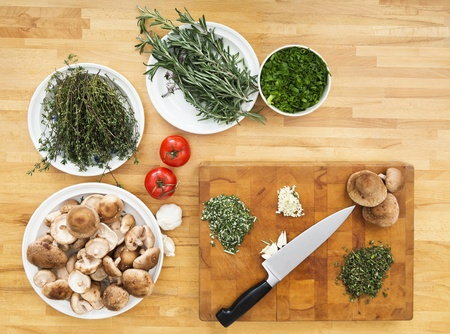 Various types of vegetables and chopping board with knife on kitchen counter photo
