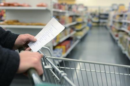 Hand schiebt einen Einkaufswagen durch die Gänge eines Supermarktes, hält eine Liste mit Lebensmitteln, mit den täglichen Bedarf in Handschrift auf einem Zettel