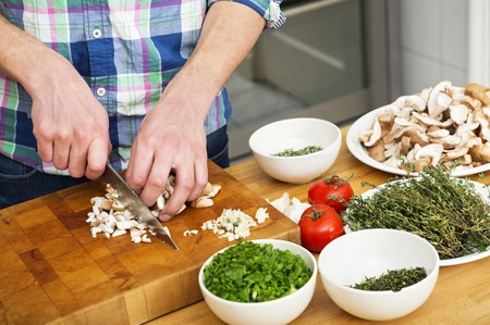 Midsection of man chopping mushrooms with vegetables on counter in kitchen Stock Photo - 17169414