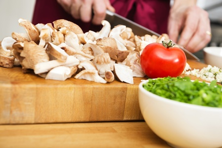 Midsection of man cutting mushrooms with bowl of chopped spring onions in front photo