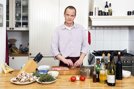 Portrait of Caucasian man preparing meat at kitchen counter Stock Photo - 17289611
