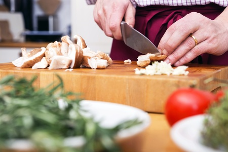 Midsection of man cutting mushrooms on chopping board Stock Photo - 17169423