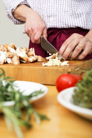 Midsection of man cutting mushrooms on wooden chopping board Stock Photo - 17169420