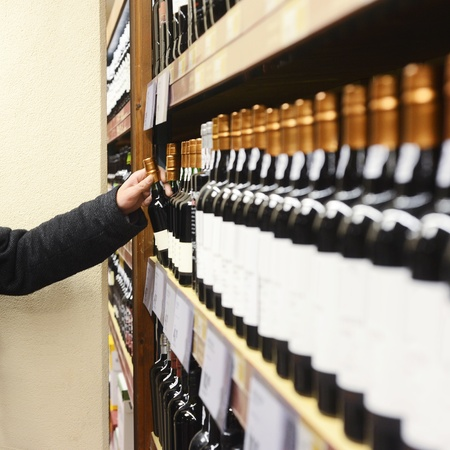Caucasian man in jacket choosing wine bottle from shelves in store