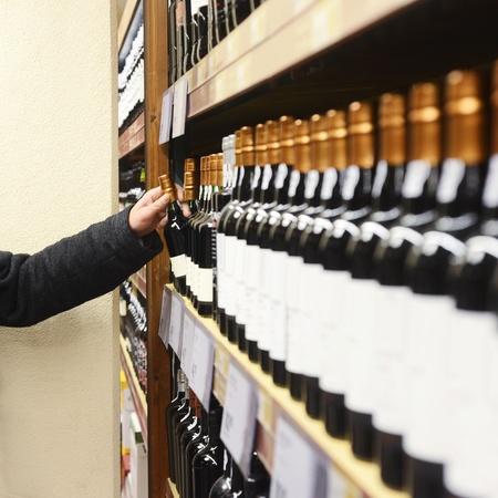 beverage display: Caucasian man in jacket choosing wine bottle from shelves in store