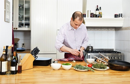 meat counter: Caucasian man cutting meat on chopping board at kitchen counter Stock Photo