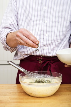 Midsection of man sprinkling thymes in batter Stock Photo - 17169408