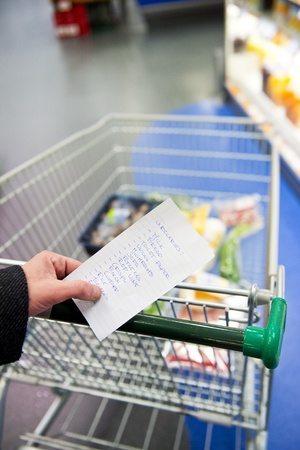 necessities: Hand, holding a shopping list with day to day groceries and other necessities, whilst pushing a shopping cart through a supermarket Stock Photo