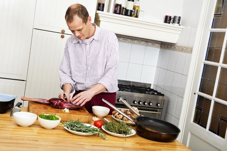 meat counter: Caucasian man preparing meat at kitchen counter Stock Photo