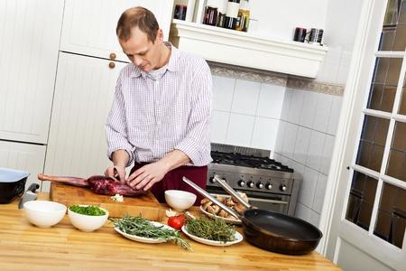 Caucasian man preparing meat at kitchen counter Stock Photo - 17289609