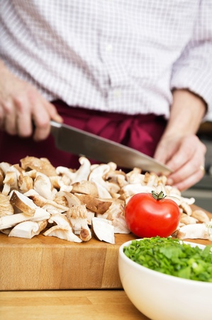 Tomato surrounded by cut up mushrooms  on chopping board, with the midsection of man with a knife, cutting, out of focus in the background Stock Photo - 17169411