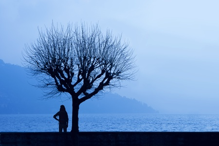 Silhoette of a hiker admiring the hazy winter dawn of a lake with misty mountains in the background underneath a tree (Lago di Como, Italy) photo