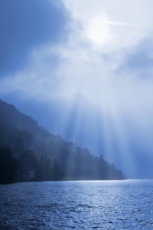 breaking through: Sol que se rompe a trav�s de las nubes sobre las monta�as brumosas que rodean el lago de Como, Lombard�a, Italia
