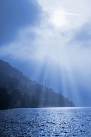 Sun breaking through the clouds over the misty hills surrounding lake Como, Lombardy, Italy photo