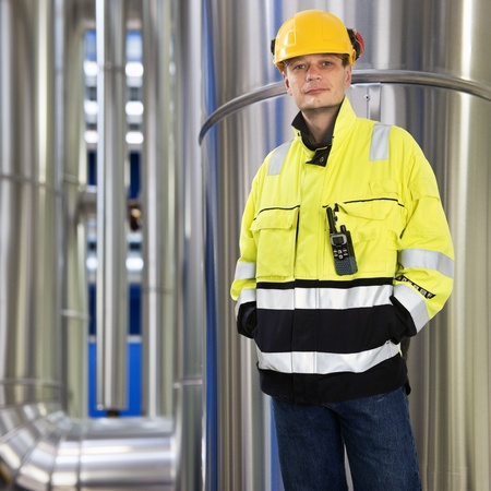 ear muffs: Engineer, wearing protective clothing, a hard hat with ear muffs connected standing with his hands in his pockets, looking kindly into the camera in front of the large stainless steel pipes in a huge boiler room Stock Photo