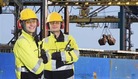 safety glasses: Two dockers, coworkers and colleages, wearing the same outfit, posing in front of a large transport ship, where raw materials, such as iron ore are being unloaded at an industrial harbor