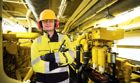 mecanica industrial: Mecánico orgulloso, posando con los brazos cruzados, un casco, gafas, guantes y un abrigo reflexivo en la sala de máquinas de un buque de suministro mar adentro industrial