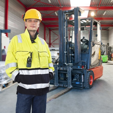 Man, waring safety clothes, including a hard hat, standing proudly in front of his forklift truck in a warehouse Stock Photo - 17382744