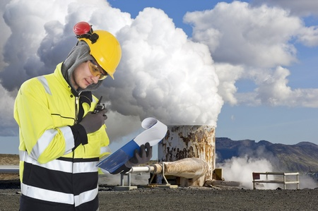 energy work: Geothermal engineer and geologist reading data from a list at a gothermal power plant in Iceland, creating hot water and sustainable energy from natural resources