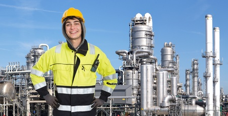 retardant: Ingegnere chimico felice, orgoglioso e fiducioso, sorridente nella fotocamera di fronte a un plabnt petrolchimico, con i cracker in acciaio inox, torri di distillazione, e un paio di colonne di fumo in background Archivio Fotografico