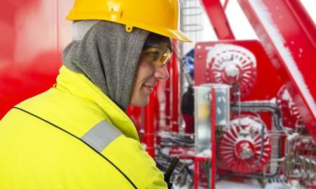 Shipping engineer on a cold winter day, on the snowy bridge of an offshore support vessel, wearing a hoodie and safety gear, such as a hard hat, goggles and reflective coat Stock Photo - 17382750