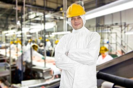 production plant: Sorridente operaio in una fabbrica di lavorazione della carne e macello, indossando abiti igienico