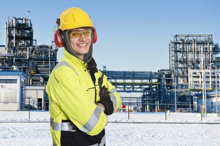 Industriearbeiter, posiert vor dem Haupttor einer großen Chemiefabrik. Winterzeit. Glückliche Ingenieur, tragen alle Schutzkleidung notwendig ist, wie Gehörschutz, einem harten Hut, chemikalienbeständig reflektierenden Mantel, Handschuhe und Schutzbrille tragen. Proudl