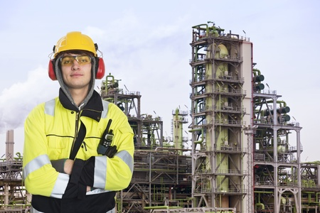 walkie: Young chemical engineer posing in front of a biodiesel refinary plant, wearing a hard hat, fire retardant clothing with reflective stripes, looking proudly into the camera