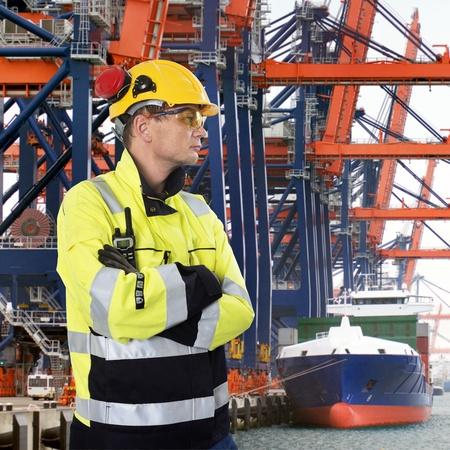 Docker, trägt einen Schutzhelm, Handschuhe, Schutzbrille und chemikalienbeständig Mantel, streng mit Blick auf einen Industriehafen mit großen Kränen, Entladen von Containern von einem Frachtschiff
