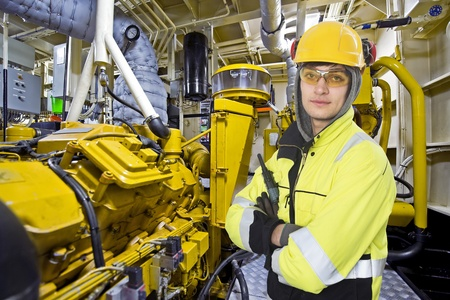 Mechanical engineer posing in the engine room of an offshore supply vessel