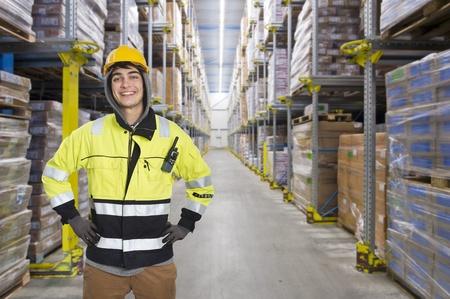Lächelnd, mit Kapuze Mann, mit einem harten Hut in einem riesigen Kühlhaus Lager Standard-Bild