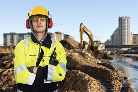 safety jacket: Young construction engineer posing in front of the muddty construction site of a large building project Stock Photo