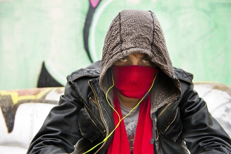 juvenile delinquent: Hooded figure, wearing a scarf in front of his nose and mouth to disguise himself, looking menacing into the camera Stock Photo