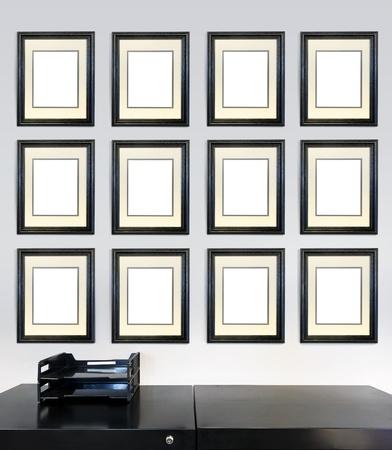 Douze certificats de mérite encadré pour employé des images mois sur un mur dans un bureau, devant un classeur.