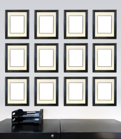 Twelve framed award certificates for employee of the month images on a wall in an office, in front of a file cabinet. Stock Photo - 19108698