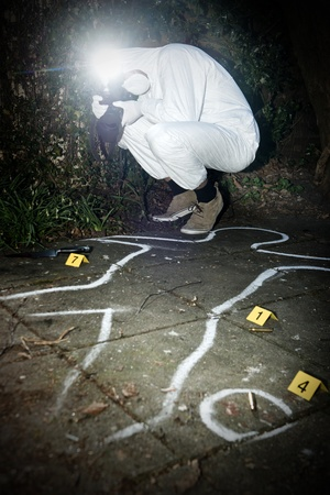 Crime scene photographer taking a photo fo during the forensics research of a murder in a park
