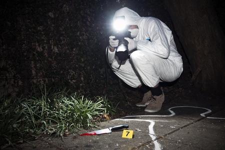 escena del crimen: Forensics investigador fotografiar un cuchillo manchado de sangre en la escena del crimen Foto de archivo
